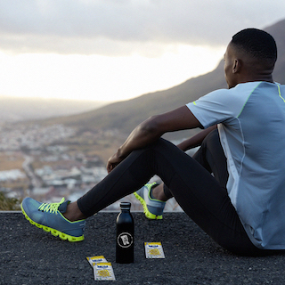 Man Looking out over City & Mountains after Long Run