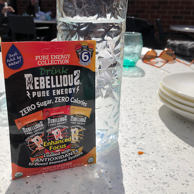 Rebellious Pure Energy 6-count Variety Pack on Table next to Glass Water Bottle