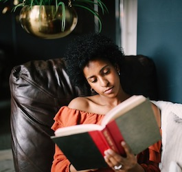 Woman Reading Book on Black Leather Chair