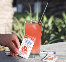 Outdoors Photo of Glass of Drink Rebellious with Hand Raching to pick up liquid packet of Blood Orange Flavor