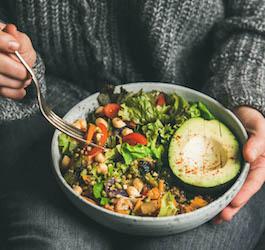 Woman in Grey Sweater Eating Avocado Salad