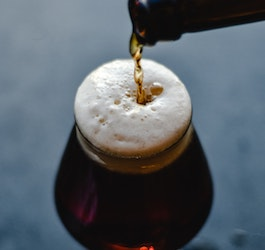 Pouring Dark Brown Beer from Bottle into Glass