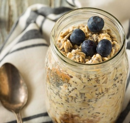 Jar Containing Grapefruit and Ginger Chia Seed Pudding Topped with Blueberries