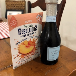 Bottle of Prosecco and Rebellious Peach 12-pack on Table