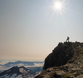 Hiker at Top of Mountain Looking out Across Mountain Range
