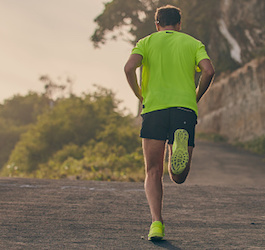 Man in Bright Green Shirt and Black Shorts Running Uphill in Street