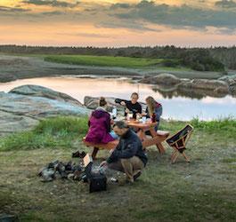 Group Sitting at Picnic Table Eating Camp Food