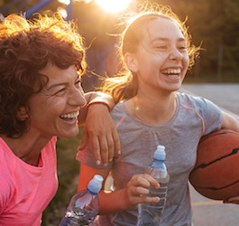 Two Women Laughing Outside while Taking a Hydration Break during Basketball