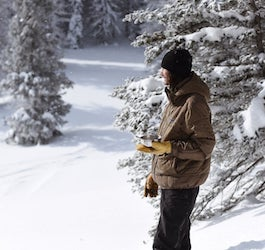 Skier Standing Holding Bowl of Food in Snowy Scene