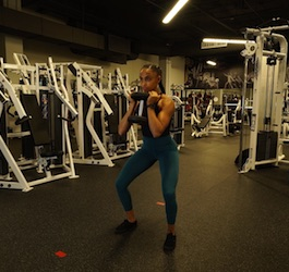 Woman Performing Goblet Squat Surrounded by Gym Equipment