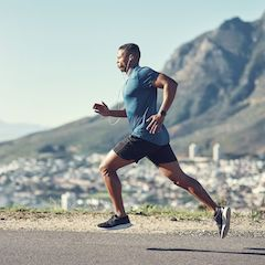 Man Running Mid-Stride with City and Mountain in Background