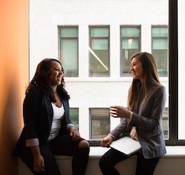 Two Women Sitting on Window Ledge Talking (wocinetechchat via Unsplash)