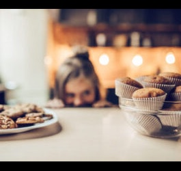 Woman Peeking over Table, Eyeing Muffins and Cookies