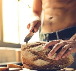 Shirtless Man Slicing Large Loaf of Bread