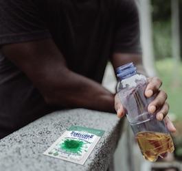 Man Drinking Mint Leaning on Railing