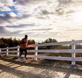 Man Running on Gravel Trail Next to White Rail Fence