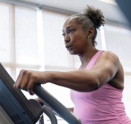 Woman in Pink Top on Exercise Machine