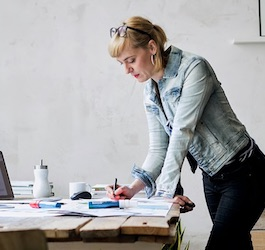 Woman in Jean Jacket Standing at Desk Writing
