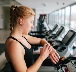 Woman on Treadmill Checking Fitness Tracker