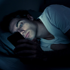 Man Laying on Side in Bed Reading Phone