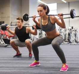 Man and Woman Doing Squats with Weights in Gym