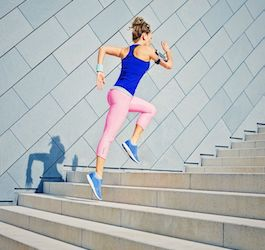 Woman in Blue Top and Pink Leggings Running up Steps