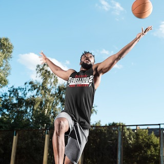 Man Leaping to Rebound Basketball and Wearing Drink Rebellious T-shirt with Ripped Sleeves