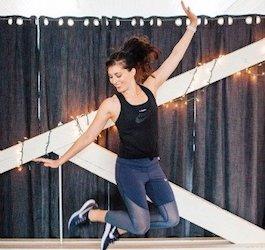 Woman wearing black tank top and blue leggings leaping in air