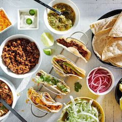 Overhead Photo of Tacos in a Rack with Various Toppings & Ingredients