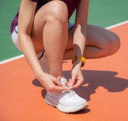 Woman in Running Gear Tying Running Shoe on Track