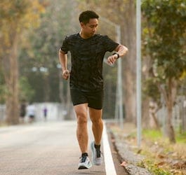 Man Checking Watch while Running on Side of Road