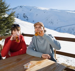 Couple drinking Rebellious Infusions—Peach on outdoor deck with snowy mountains in background