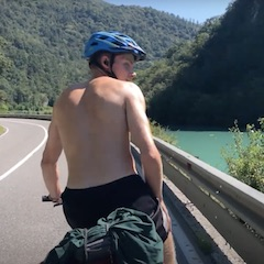 Shirtless Man Cycling on Road Next to River