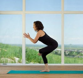Woman Exercising on Yoga Mat in Front of Large Windows