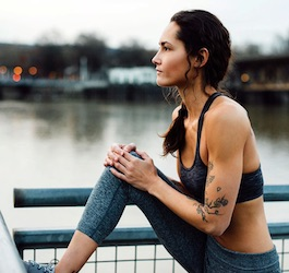 Woman Stretching after Workout with Harbor in Background