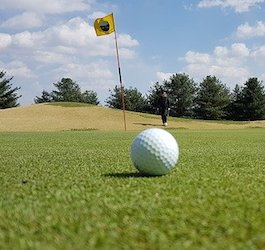 Golf Ball on Green with Pin and Golfer in Background