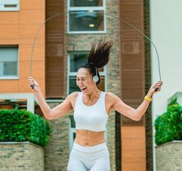 Woman Jumping Rope in Front of Building