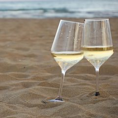 Two Glasses of White Wine on Sandy Beach