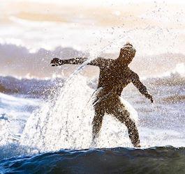 Man Riding Surfboard in Long Set of Medium Waves