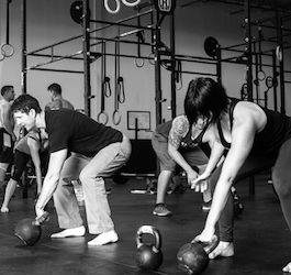 Group of People Exercising with Kettlebells in Fitness Center