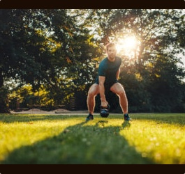 Man and Kettlebell on Lawn with Sun in Background