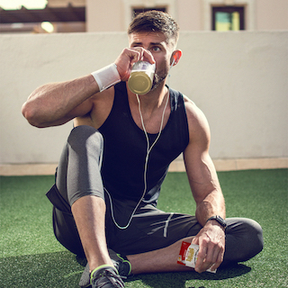 Man in Workout Clothes Sitting on Turf Drinking Rebellious Caffeine-Free Infusions—Sangria