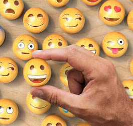 Man Holding One of Several Emoji Buttons