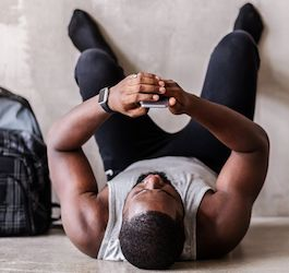 Man Laying on Floor with Feet on Wall Looking at Phone