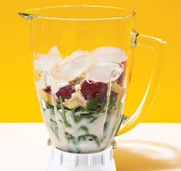 Blender Filled with Ice Fruit Green and More with Bright Yellow Wall in Background