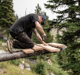 Man using cordless drill to build snowboard ramp