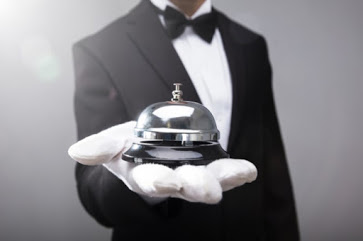 butler with outstretched hand holding bell