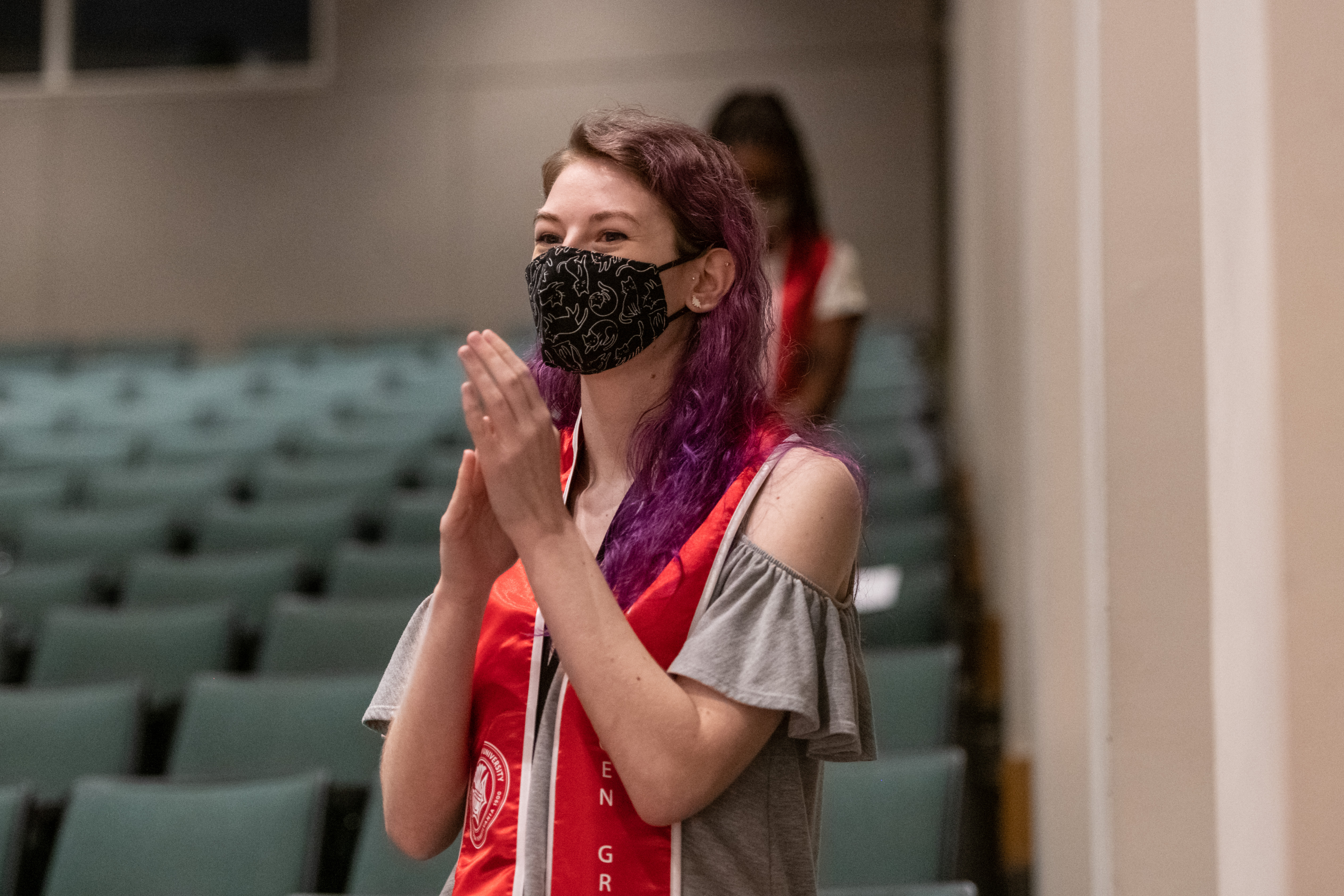Student with purple hair and a black mask stands and claps in a crowd.