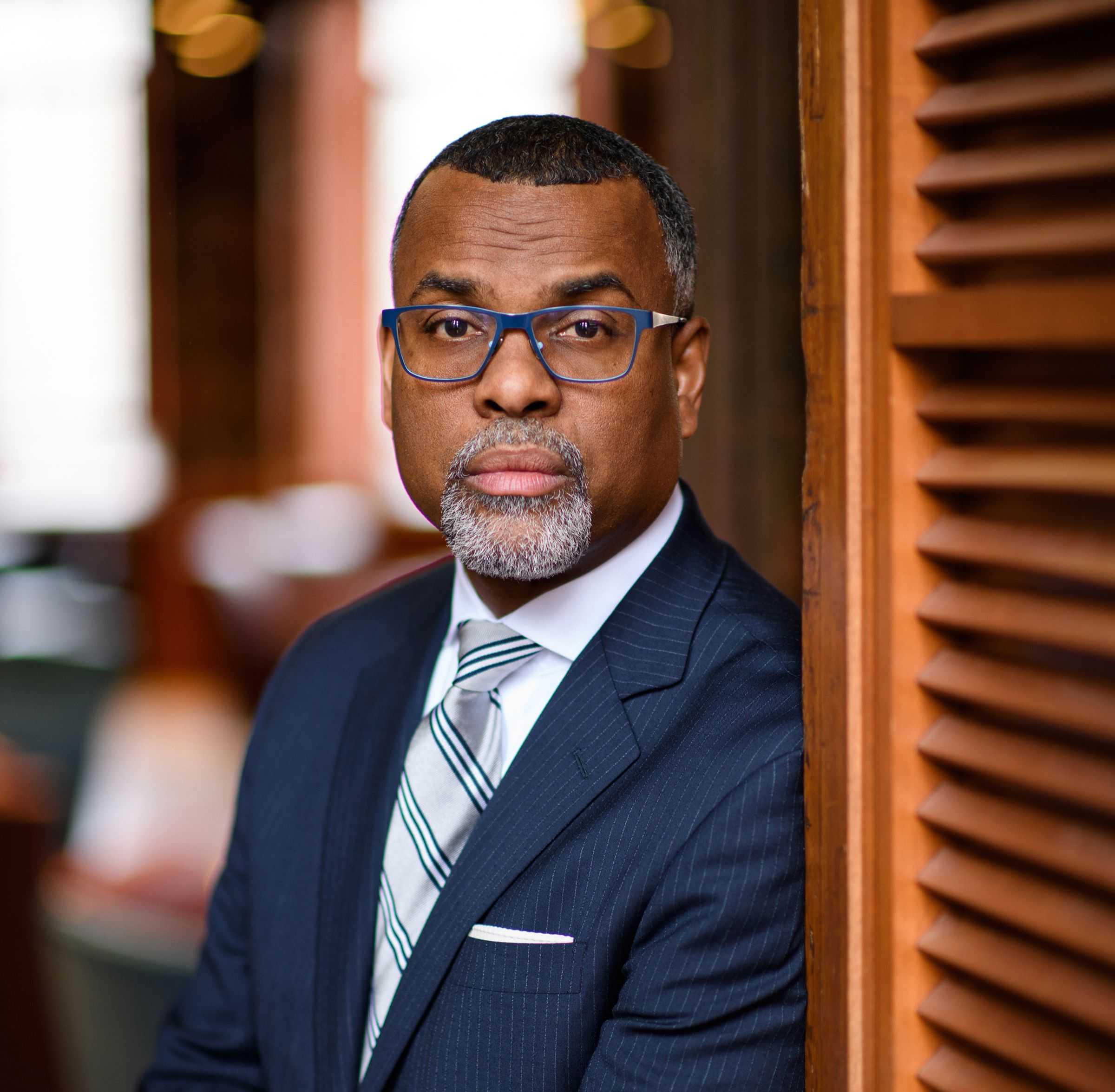 Dr. Glaude wearing a navy suit and leaning against a wall.