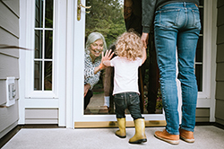 todler talking to grandmother through glass door